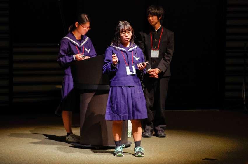 Three students on stage