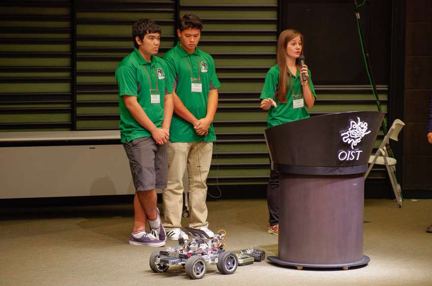 Three students on stage with a robot